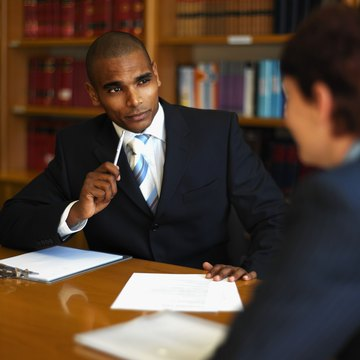 front view of businessman interviewing side view businesswoman sitting