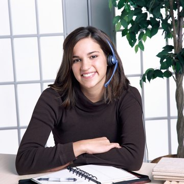 A young adult Caucasian female wearing a telephone headset while she looks at the viewer