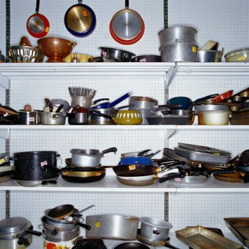 Used pots and pans on store shelf in thrift store, full frame