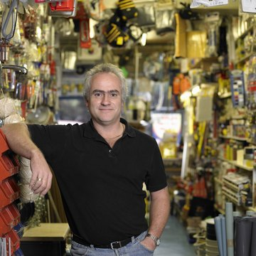 Man in hardware shop, hand in pocket, smiling, portrait