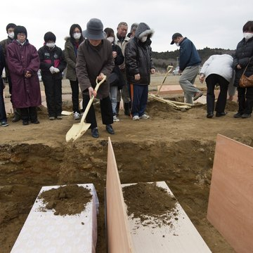 Dirt being shoveled onto coffins in China
