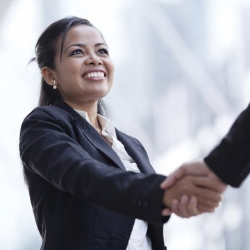 Businesswoman giving a handshake and smiling