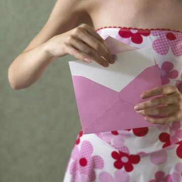 Woman taking card out of handwritten envelope.