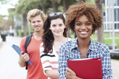 Three students smiling on college campus