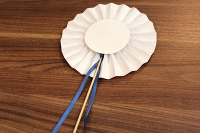 Hot glue a dowel and ribbon to the rosette