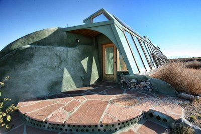 Cans, tires and bottles serve as building materials for an Earthship.