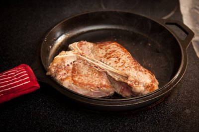 Steak cooking in a cast-iron skillet.