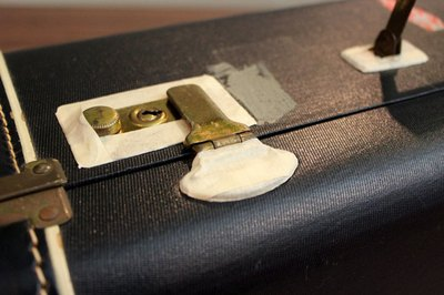 Cover luggage hardware with masking tape