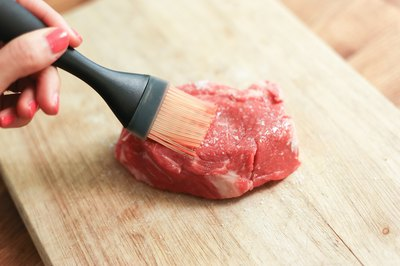 Brushing oil on a top sirloin steak.