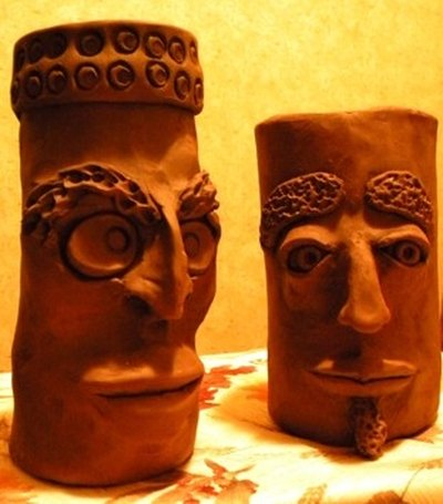 Grotesque face jugs fired in homemade outdoor kiln
