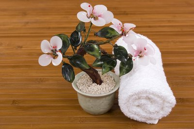 Rolled up white towels and small potted plants can serve as spa decor.