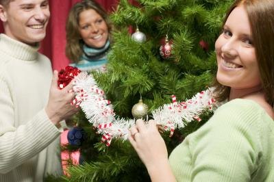 3 people smiling and decorating a Christmas tree.