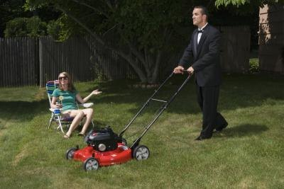 Man in suit mowing lawn slowly.