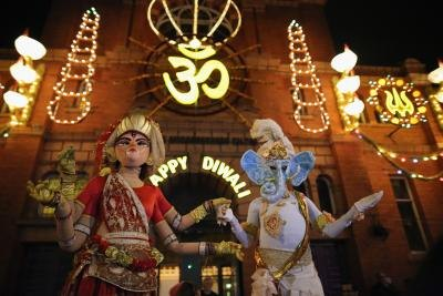 Costumed revelers dressed as Lord Genesha and Goddess Lakshmi during Diwali festival
