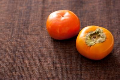 2 persimmons on a brown background.