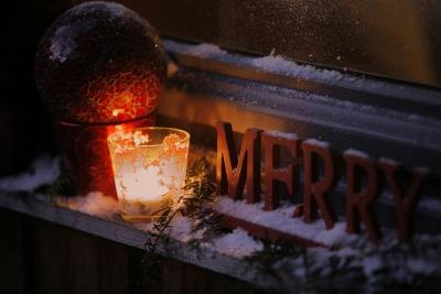 Candles next to a Merry Christmas sign.