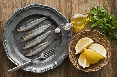 Fresh raw sardines with a side of lemon slices and parsley