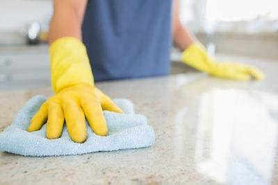 A close up of a man wiping down a counter.