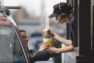 A fast-food employee hands a customer her order from a drive-thru window.