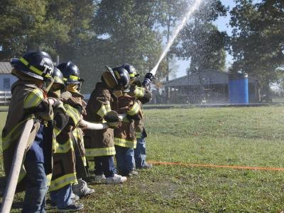 Young children learning how to be firefighters.
