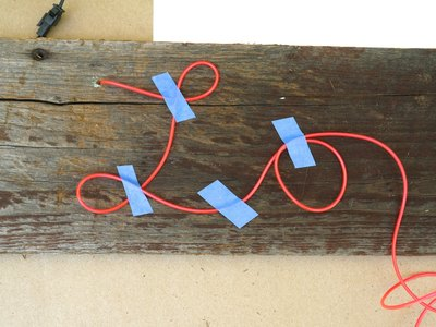 Bend the EL wire into letters and secure with tape.
