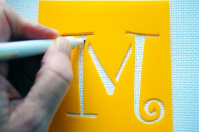 Stenciling a letter onto fabric.