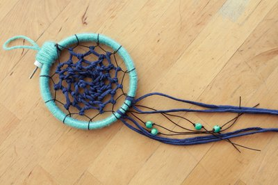Tie beads, feathers or tails of yarn to the base of your dreamcatcher.