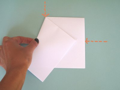 Fold the left corner of the paper down to the center.