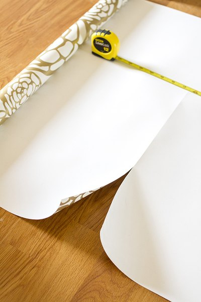 Cut a piece of wallpaper off the roll that is 6 inches longer on each end.