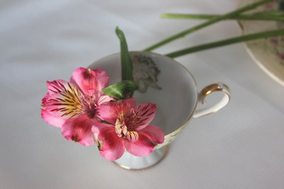 Start by adding the shortest flowers around the edge of the teacup.