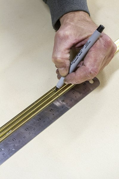 Mark brass pipes using a ruler and marker.