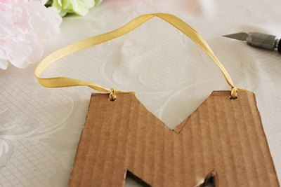 Tie the ribbon onto the cardboard letter.