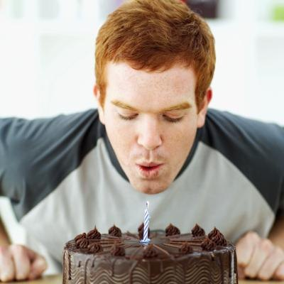 Man blows out candle on birthday cake