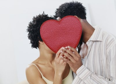 A man and woman are kissing behind a red heart.