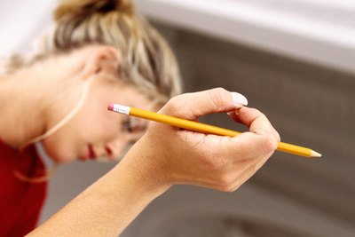 A woman holds a pencil while thinking.