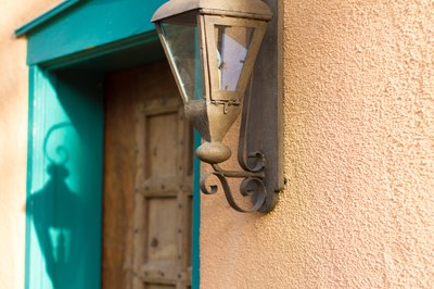 A close-up of a rustic light fixture next to a wooden door with turquoise trim on a stucco home.
