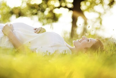 Pregnant woman smiling, lying in grass