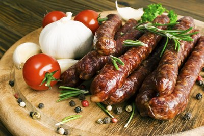 Pork sausages on a cutting board with onions and tomatoes.