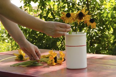 A woman filling a vase with freshly picked black-eyed susans.