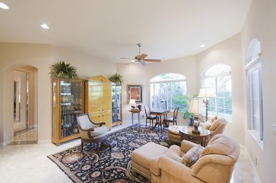 A carpeted living room has a large area rug on it.