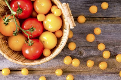 An overhead view of a basket of red and yellow tomatoes.