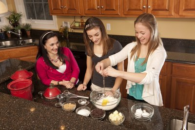 Three girls baking in a kitchen.