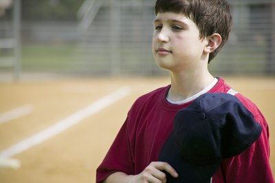 A young boy holds his baseball hat over his heart while singing the anthem