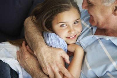 A grandfather hugs his granddaughter.
