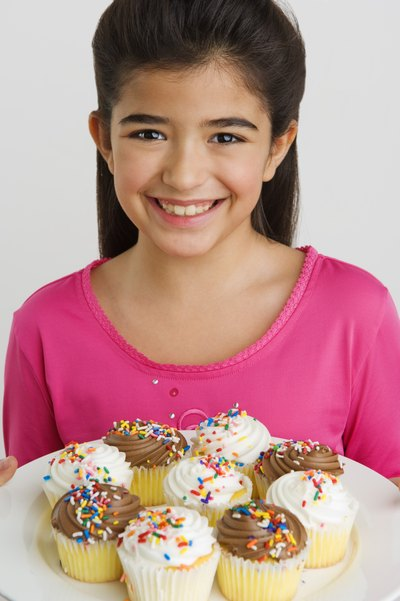 Girl holding cupcakes