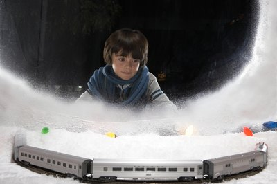 Young boy looking at train display in window