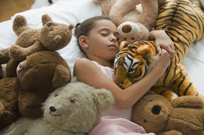 Girl sleeping with stuffed animals