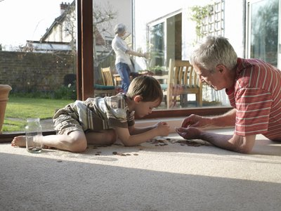 Grandson and Grandfather counting coins on floor