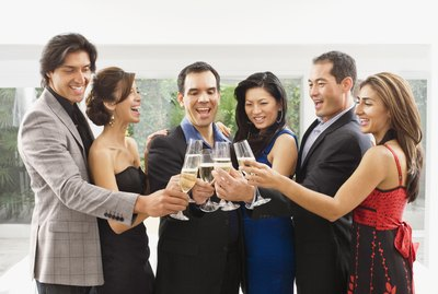 Couples in fancy clothes are toasting with wine glasses.