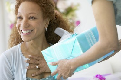 A woman happily recieves a present.